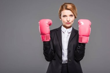 serious businesswoman posing in suit and pink boxing gloves, isolated on grey