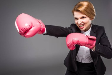 angry businesswoman in pink boxing gloves, isolated on grey