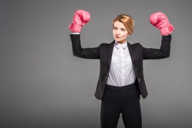 strong businesswoman posing in boxing gloves, isolated on grey