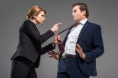 angry female boss pointing at businessman in formal wear, isolated on grey