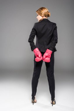 rear view of businesswoman posing in suit and pink boxing gloves, isolated on grey