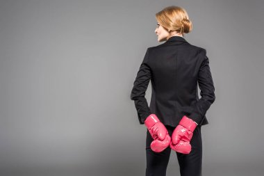 back view of businesswoman in suit and pink boxing gloves, isolated on grey