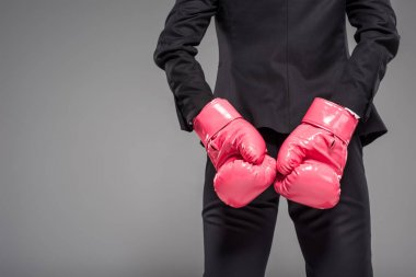 partial view of businesswoman in pink boxing gloves, isolated on grey
