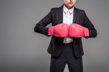 cropped view of strong businesswoman posing in boxing gloves, isolated on grey