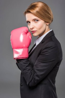 beautiful businesswoman in suit and pink boxing gloves, isolated on grey
