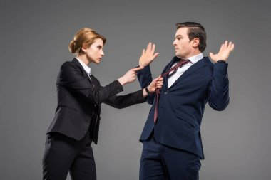 aggressive businesswoman holding tie and pointing at stressed coworker, isolated on grey