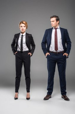 confident businesswoman and businessman standing with hands in pockets, isolated on grey