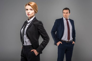 confident businesswoman with hands in pockets and businessman standing behind, isolated on grey, feminism concept