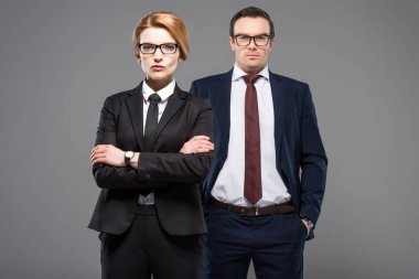 confident businesswoman with crossed arms and serious businessman, isolated on grey