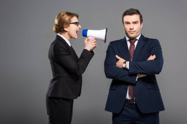 aggressive businesswoman with bullhorn yelling at businessman, isolated on grey, feminism concept