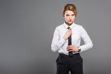 confident businesswoman in white shirt and tie, isolated on grey