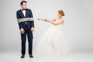 bride bounding groom with rope, isolated on grey, feminism concept