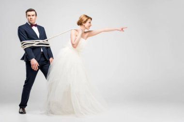 bride pointing and pulling groom bound with rope, isolated on grey, feminism concept