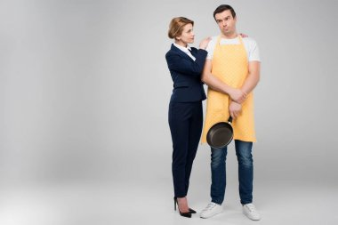 businesswoman and male upset householder with frying pan hugging together, feminism concept, isolated on grey