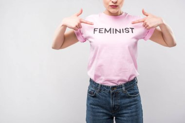 cropped view of woman pointing at pink feminist t-shirt, isolated on grey