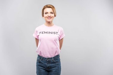 smiling woman in pink feminist t-shirt, isolated on grey