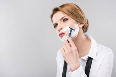 beautiful businesswoman shaving face her face, isolated on grey, feminism concept