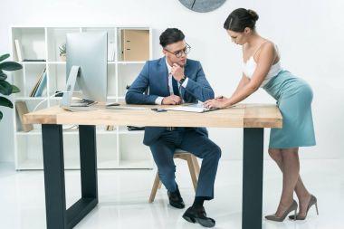 secretary talking to boss at office