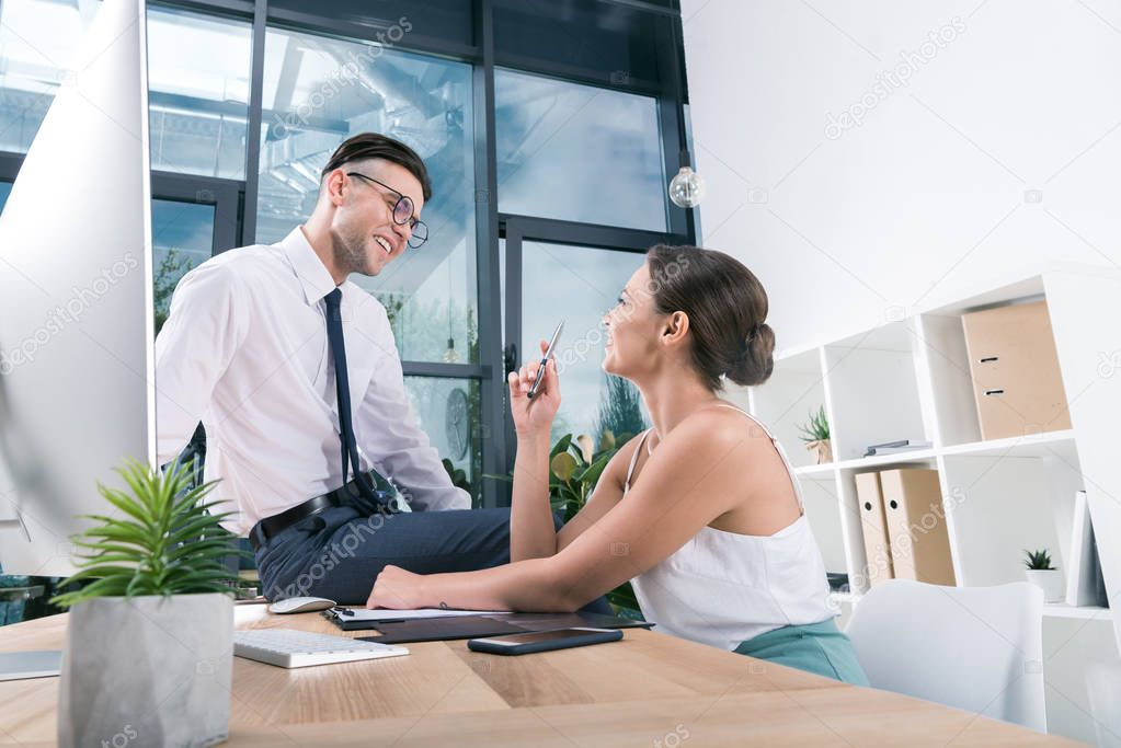 smiling businesspeople talking at workplace in office