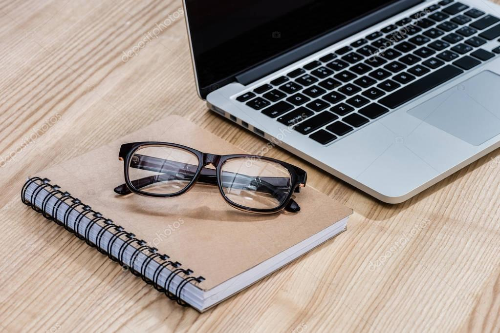 eyeglasses and notebook on table