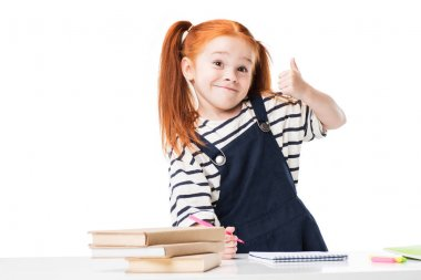 Adorable smiling redhead schoolgirl drawing with felt tip pens and showing thumb up isolated on white stock vector