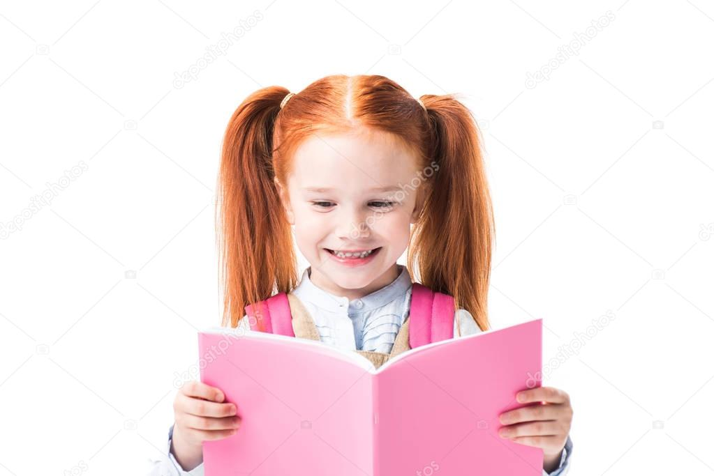 Smiling schoolgirl reading textbook