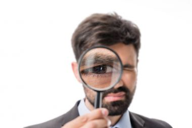 Portrait of businessman looking at camera through magnifying glass isolated on white stock vector