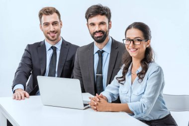 Portrait of smiling business people looking at camera while sitting at workplace with laptop stock vector