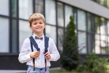 cheerful schoolboy near school