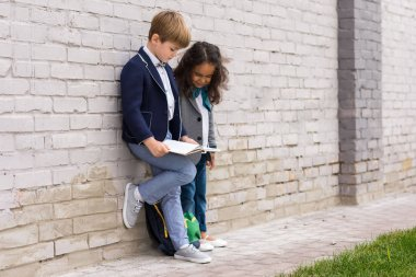 multiethnic schoolkids reading book