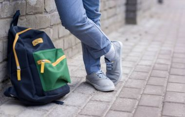 schoolboy with backpack on street