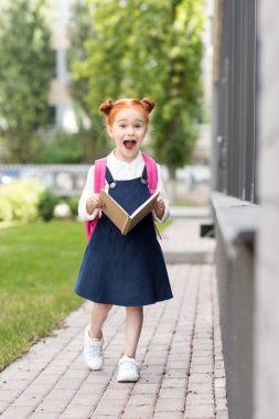 redhead schoolgirl holding book
