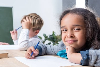 multiethnic schoolkids drawing in class