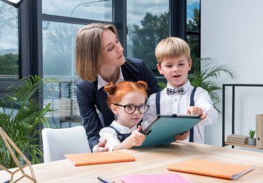 teacher with schoolkids using digital tablet