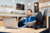 Uomo daffari che utilizza computer portatile nella caffetteria