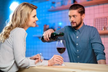bartender pouring wine to woman