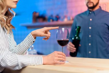 Cropped shot of young woman pointing at glass of red wine while bearded bartender holding bottle stock vector