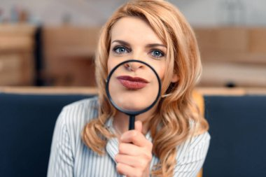 Young blonde businesswoman looking through magnifying glass stock vector