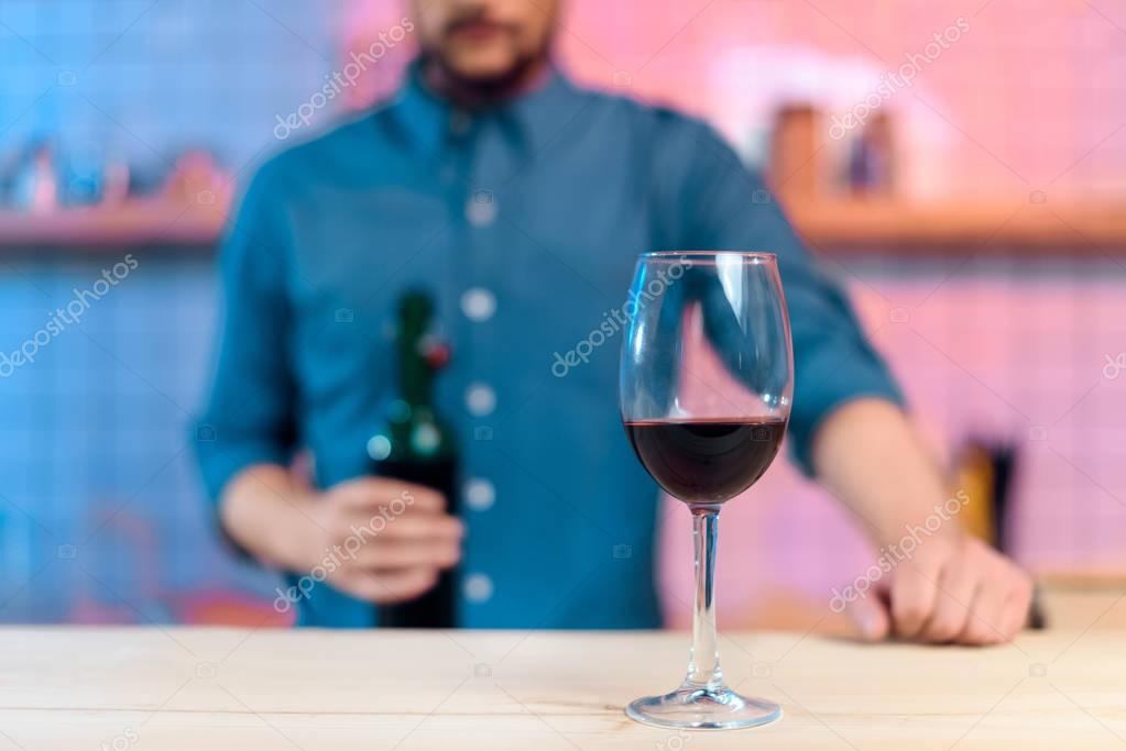 man pouring wine in glass