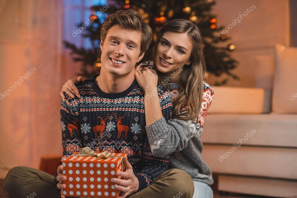 woman hugging boyfriend with christmas gift