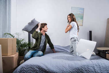 Couple having pillow fight at home