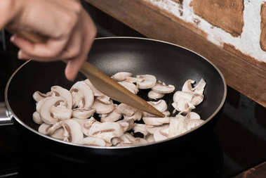 woman cooking mushrooms for dinner