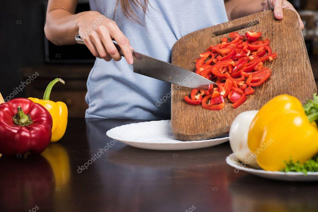 woman preparing pepper for dinner