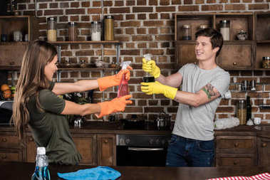 couple having fun while cleaning home