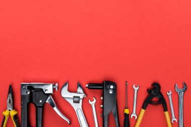 Top view shot of different reparement tools - wrenches, pliers, industrial stapler, isolated on red stock vector