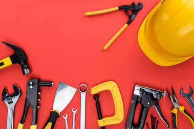 Top view shot of different reparement tools and hard hat, isolated on red stock vector
