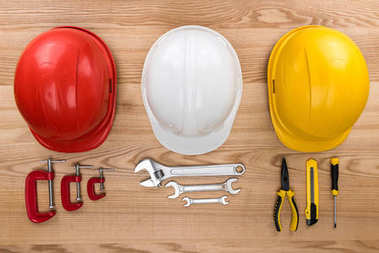 Top view shot of three various coloured hardhats and reparement tools on wooden surface stock vector