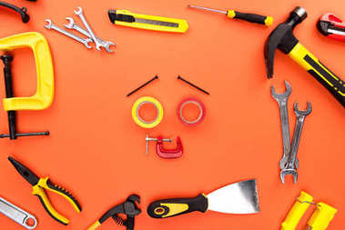 Top view shot of smiley face made of rolls of tape, screws and c-clamp, placed on orange surface with various reparement tools scattered around stock vector