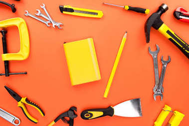 yellow notebook and reparement tools