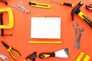 Top view shot of composition with open notebook and pencil, placed on orange surface with various reparement tools scattered around stock vector